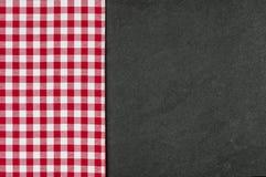 有一张红色方格的桌布的板岩板材 免版税库存图片