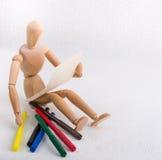 有一张纸的一个木玩偶和色的笔 免版税库存图片