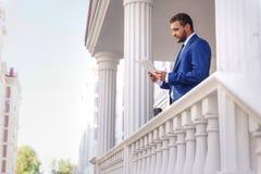 有一张纸的典雅的成熟人在大阳台 免版税图库摄影