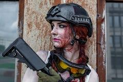 有一张血淋淋的面孔的美丽的军队女孩与在伪装的步枪在都市场面穿衣,得到休息画象,关闭  图库摄影