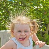 有一张滑稽的面孔的小女孩 库存照片