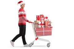 有一手推车的年轻人有戴圣诞老人帽子的礼物的 库存照片