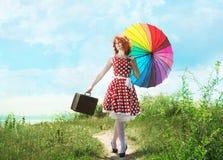 有一把五颜六色的伞的减速火箭的女孩 免版税图库摄影