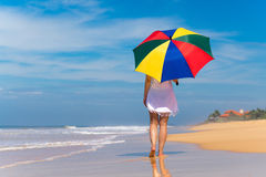 有一把五颜六色的伞的女孩在沙滩 库存图片