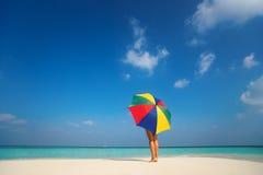 有一把五颜六色的伞的女孩在沙滩 免版税库存照片