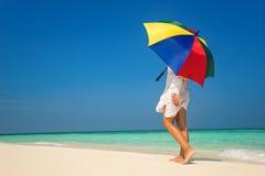 有一把五颜六色的伞的女孩在沙滩 图库摄影