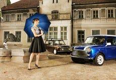 有一把伞的一名妇女在汽车和修造的bg 图库摄影