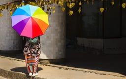 有一把伞的女孩在大Budda旁边 免版税库存图片