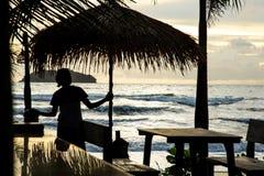 有一把伞的女孩在日落的海滩 免版税库存图片