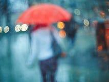 有一把伞的女孩通过与雨的一块玻璃滴下 库存图片