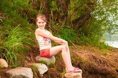 有一把伞的小女孩在湖附近的多云天 免版税库存照片