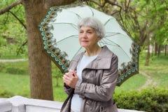 有一把伞的逗人喜爱的年长妇女前辈在游廊在公园 免版税库存图片