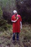 有一把刀子的可怕邪恶的小丑在森林 库存照片