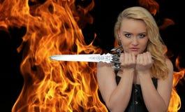 有一把刀子的年轻白肤金发的妇女在火 免版税图库摄影
