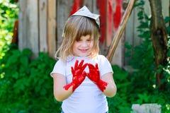 有一把刷子的女孩与红色油漆, 免版税库存图片