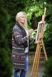 有一把刷子的妇女艺术家在她的手上在帆布画 库存照片