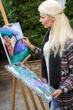 有一把刷子的妇女艺术家在她的手上在帆布画 图库摄影