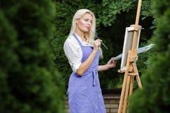 有一把刷子的妇女艺术家在她的手上在帆布画 免版税图库摄影