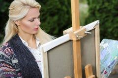 有一把刷子的妇女艺术家在她的手上在帆布画 免版税库存图片