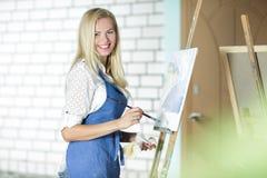 有一把刷子的微笑的妇女艺术家在她的手上在帆布画 免版税库存照片