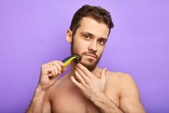 有一把剃刀的令人敬畏的帅哥在他的看照相机的面颊 库存图片