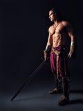 有一把剑的半裸体的战士在中世纪衣裳 库存照片