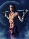 有一把剑的半赤裸战士在神秘的背景中 免版税库存照片