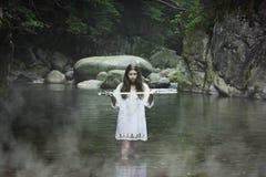 有一把剑的黑暗的女孩在山小河 免版税库存照片