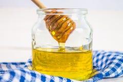有一把匙子的蜂蜜瓶子,在与一块蓝色毛巾的一张白色桌上 蜂蜜从匙子倒 库存照片