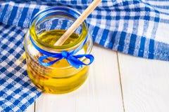 有一把匙子的蜂蜜瓶子,在与一块蓝色毛巾的一张白色桌上 免版税库存照片
