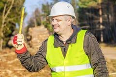 有一把卷尺的愉快的森林工程师在森林里 免版税库存图片