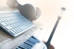 有一把吉他、一架钢琴和一台计算机的家庭演播室混合的音频的 免版税图库摄影