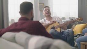 有一把吉他的一个人在朋友中在他的舒适客厅 股票录像
