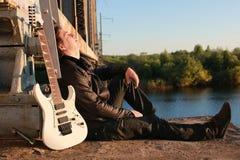 有一把吉他的人在铁路 库存图片