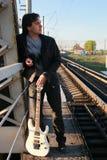 有一把吉他的人在铁路 免版税库存图片