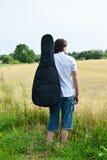 有一把吉他的人在领域 免版税库存照片