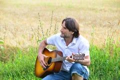 有一把吉他的人在领域 库存照片