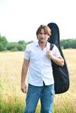 有一把吉他的人在领域 免版税库存图片