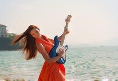 有一把吉他的女孩在海滩 免版税图库摄影