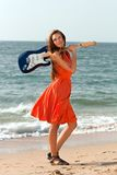 有一把吉他的女孩在海滩 库存图片