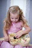 有一把吉他的小白肤金发的女孩在葡萄酒样式 免版税库存照片