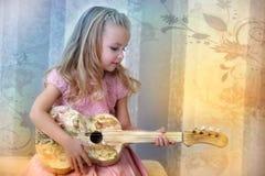 有一把吉他的小白肤金发的女孩在葡萄酒样式 库存照片
