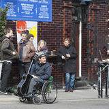 有一把吉他的音乐家在轮椅是关于客栈,听到街道音乐家音乐  免版税库存照片
