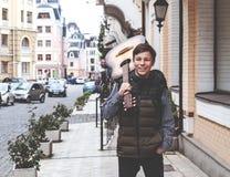 有一把吉他的年轻人在街道上 免版税库存照片