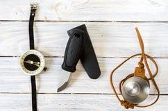 有一把固定的刀片的刀子 在皮革案件的一块玻璃 旅游业的指南针 图库摄影