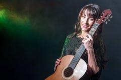 有一把声学吉他的美丽的深色的女孩在发烟性背景的手上 Copyspace 多彩多姿的背后照明 免版税库存图片
