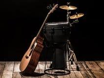 有一把声学吉他的打击乐器在木板有黑背景 免版税库存图片