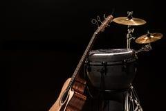有一把声学吉他的打击乐器在木板有黑背景 库存照片