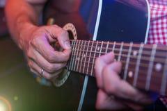 有一把声学吉他的男性音乐家 免版税图库摄影