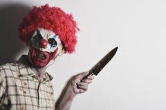 有一把大刀子的可怕邪恶的小丑 库存照片